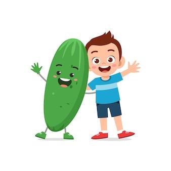 Le petit garçon mignon se tient avec le caractère de concombre