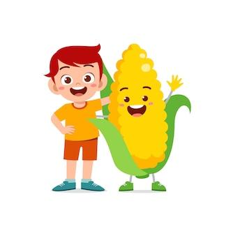 Le petit garçon mignon se tient avec le caractère de maïs