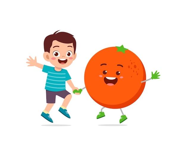 Le petit garçon mignon se tient avec le caractère orange