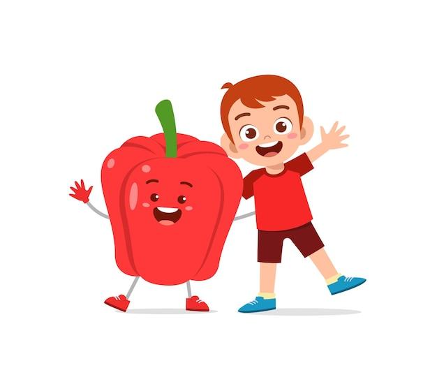 Le petit garçon mignon se tient avec le caractère de paprika