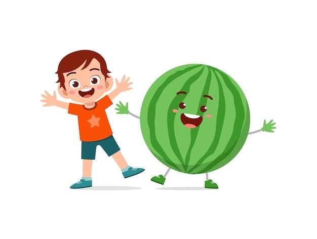 Le petit garçon mignon se tient avec le caractère de pastèque