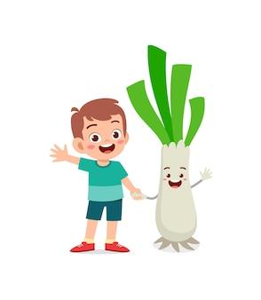 Le petit garçon mignon se tient avec le caractère de poireau