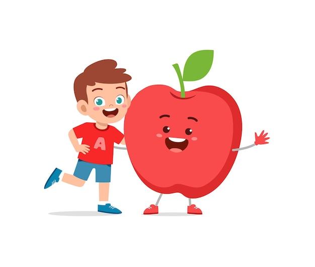 Le petit garçon mignon se tient avec le caractère de pomme