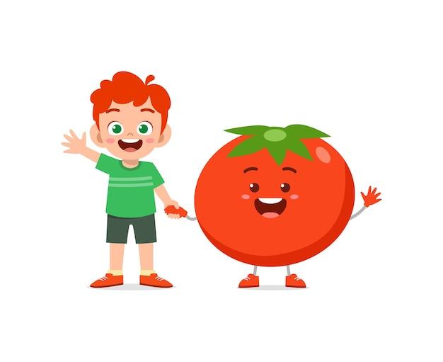 Le petit garçon mignon se tient avec le caractère de tomate