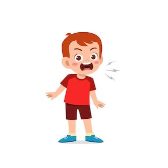 Un petit garçon mignon se tient debout et montre une expression de pose en colère