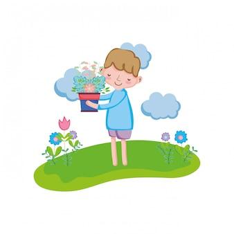 Petit garçon soulevant une plante d'intérieur dans le paysage