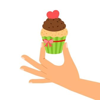 Petit gâteau avec un coeur rouge à la main,