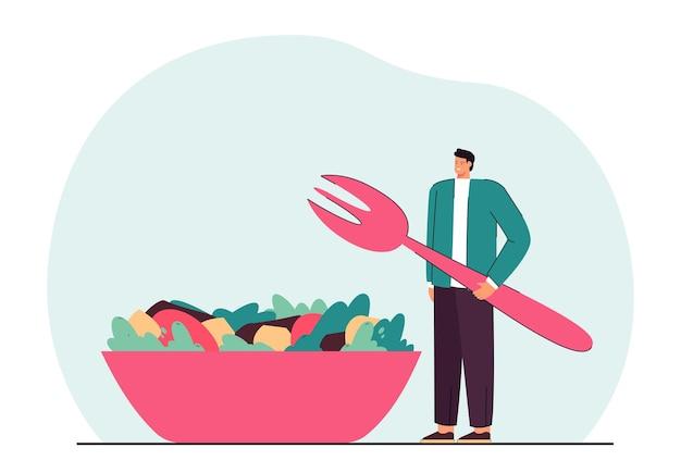 Petit homme debout à côté d'une énorme assiette avec salade de légumes
