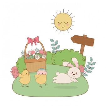 Petit lapin et poussin à l'oeuf peint dans le jardin