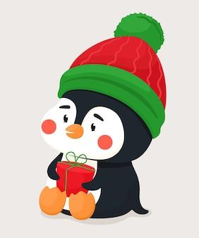 Petit pingouin mignon avec un cadeau et dans un chapeau chaud. caractère vectoriel en style cartoon plat.