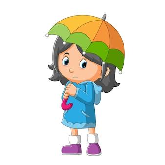 La petite fille au pull long tient le parapluie de l'illustration