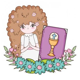 Petite fille avec une bible dans la célébration de la première communion
