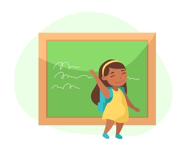 Petite fille debout au tableau noir, saluant la main