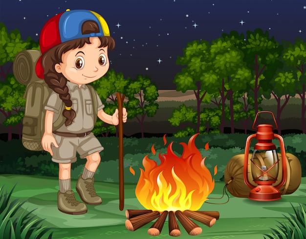 Petite fille debout près du feu de camp