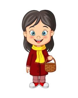 Petite fille de dessin animé dans des vêtements d'automne tenant le panier