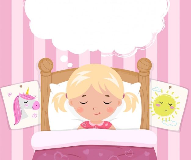 La petite fille dort dans le lit