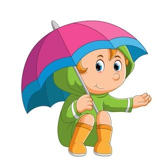 La petite fille est assise sous le parapluie et vérifie la pluie d'illustration