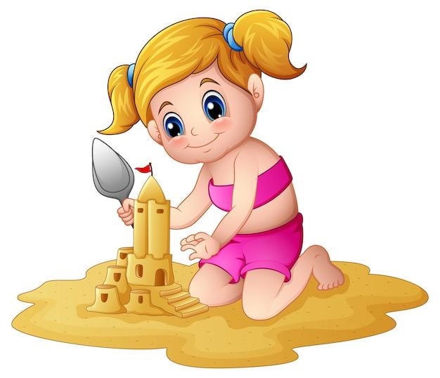 Petite fille faisant des châteaux de sable à la plage