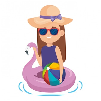 Petite fille avec flotteur flamand et ballon de plage