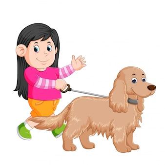 Une petite fille marche avec sa chienne en agitant sa main