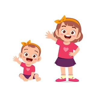 La petite fille mignonne dit bonjour avec la jeune soeur