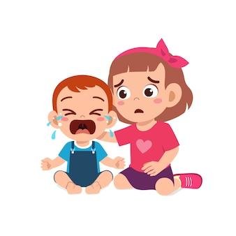 La petite fille mignonne essaie de réconforter le petit frère qui pleure