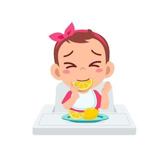 La petite fille mignonne mange des fruits et du citron aigre