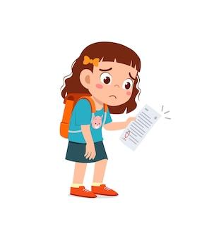 Une petite fille mignonne se sent triste parce qu'elle obtient une mauvaise note à l'examen