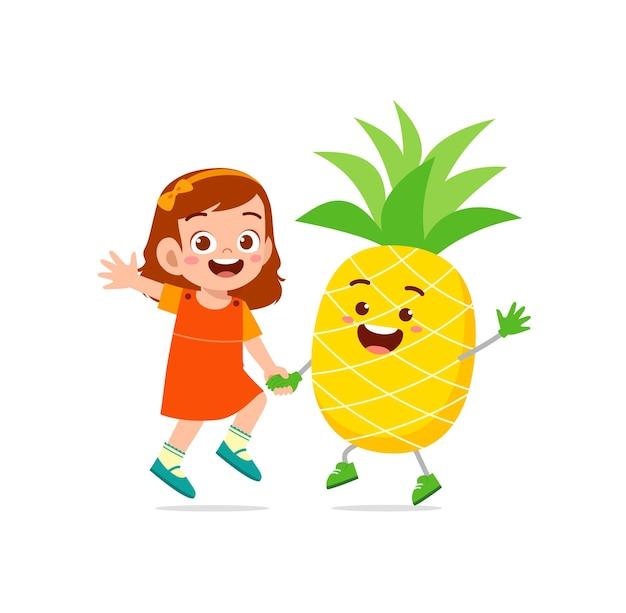 La petite fille mignonne se tient avec le caractère d'ananas