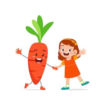 La petite fille mignonne se tient avec le caractère de carotte