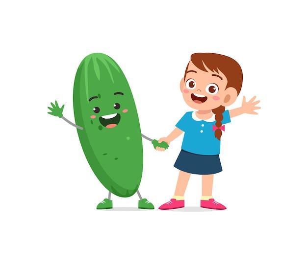 La petite fille mignonne se tient avec le caractère de concombre
