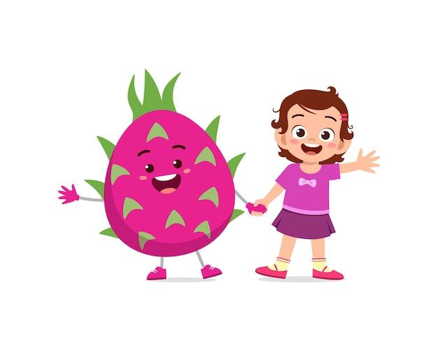 La petite fille mignonne se tient avec le caractère de fruit de dragon