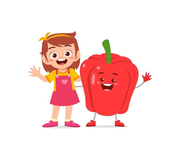 La petite fille mignonne se tient avec le caractère de paprika