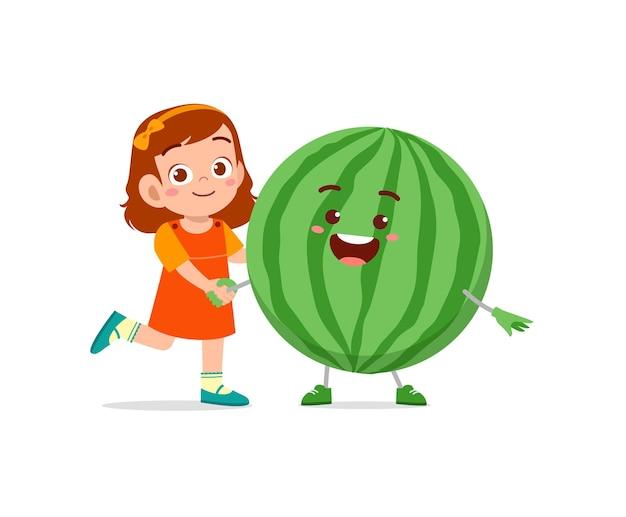 La petite fille mignonne se tient avec le caractère de pastèque