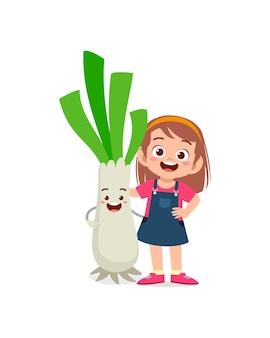 La petite fille mignonne se tient avec le caractère de poireau