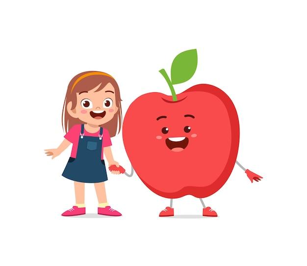 La petite fille mignonne se tient avec le caractère de pomme