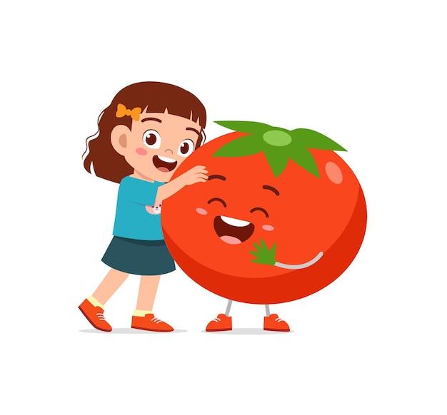 La petite fille mignonne se tient avec le caractère de tomate