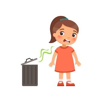 La petite fille n'aime pas la mauvaise odeur de la poubelle