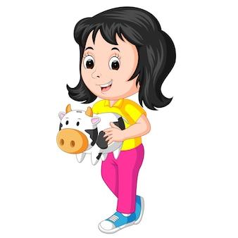 Petite fille tenant la banque de vache
