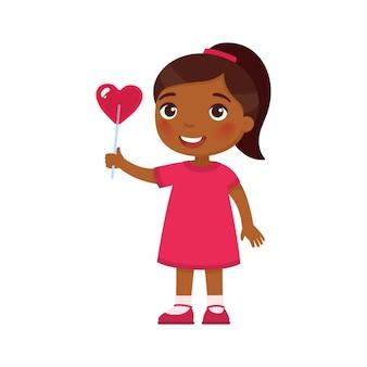 Petite fille tenant des bonbons en forme de coeur isolated on white