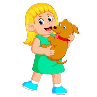 Une petite fille tient son chiot brun avec ses mains