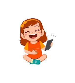 Petite fille utilisant un téléphone portable et riant