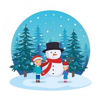 Petits enfants avec bonhomme de neige dans le paysage de neige