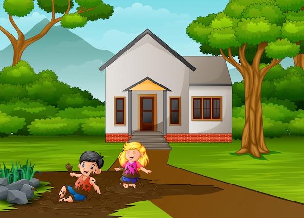 Petits enfants jouant de la boue devant la maison