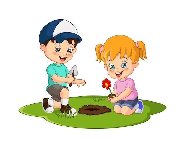 Petits enfants mignons plantant une plante fleurie dans le jardin