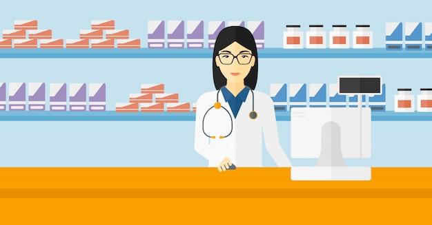 Pharmacien au comptoir avec écran d'ordinateur.