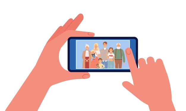 Photo de famille. mains tenant le smartphone avec photo de famille