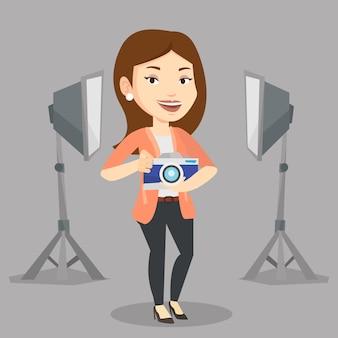 Photographe avec appareil photo en studio photo.