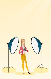 Photographe avec une caméra dans un studio photo.