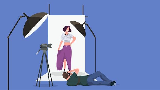 Photographe homme professionnel allongé pose tir belle femme sexy modèle posant intérieur moderne studio photo horizontal pleine longueur